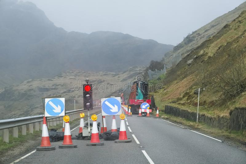 Het rode licht bij weg werkt en verkeerskegels met veiligheidsteken bij landelijke geïsoleerde bergscène stock fotografie