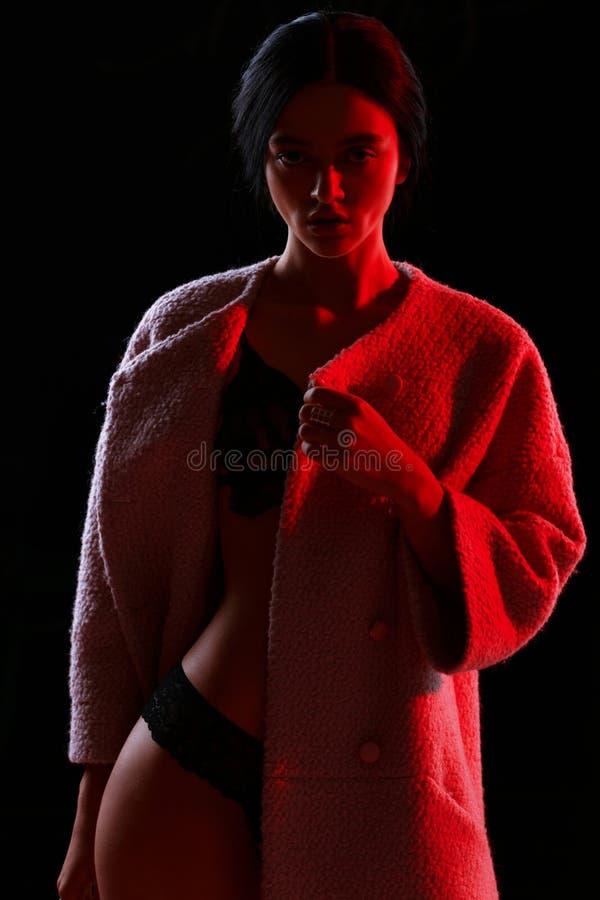Het rode licht van het maniermeisje in studio stock afbeeldingen