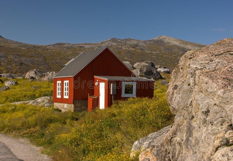 Het rode plattelandshuisje van de Visserij op geel gebied in Groenland royalty-vrije stock afbeelding