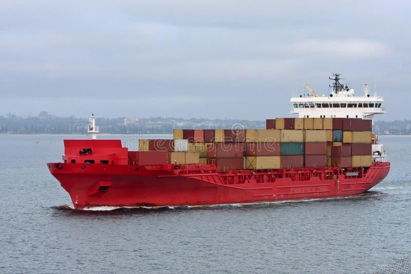 Het rode schip van de ladingscontainer op zee. stock afbeeldingen