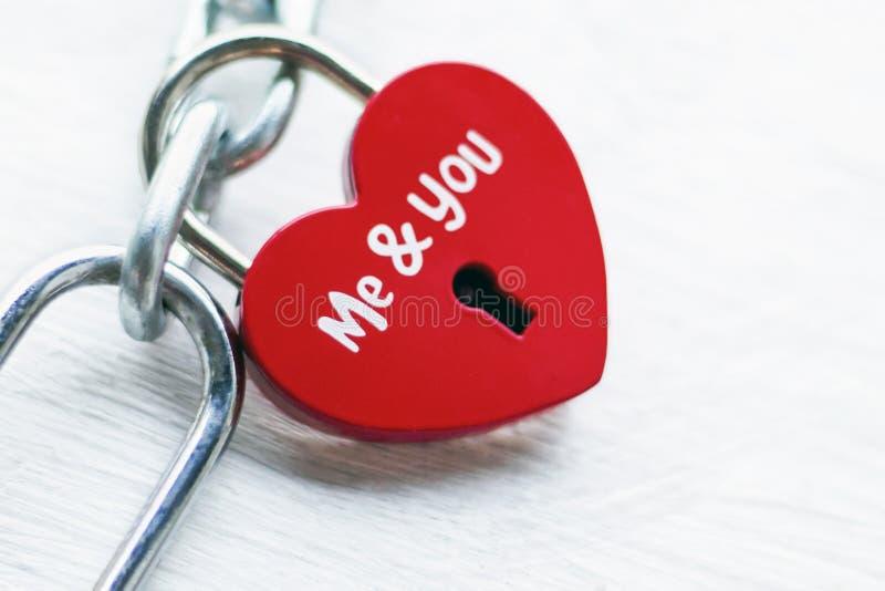 Het rode slot in de vorm van hart op een ijzerketting met een inschrijving, me en u Het concept liefde en huwelijk romanticism stock afbeelding