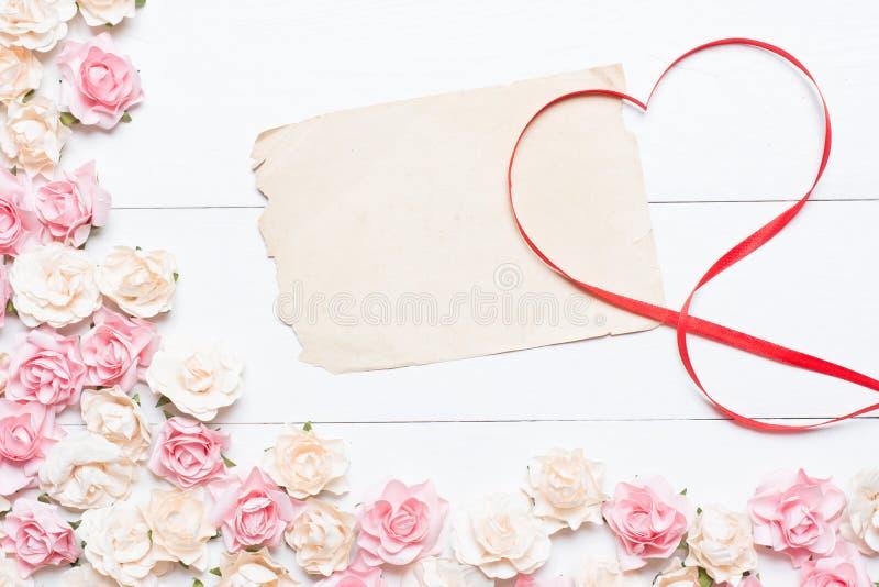 Het rode symbool van het linthart met oud leeg document blad en roze nam toe stock afbeelding
