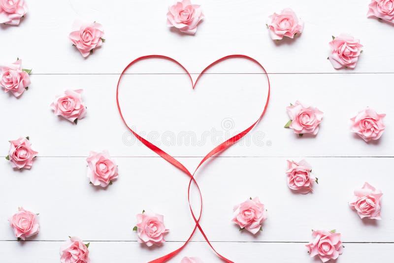 Het rode symbool van het linthart met roze rozen op witte houten lijst royalty-vrije stock foto's