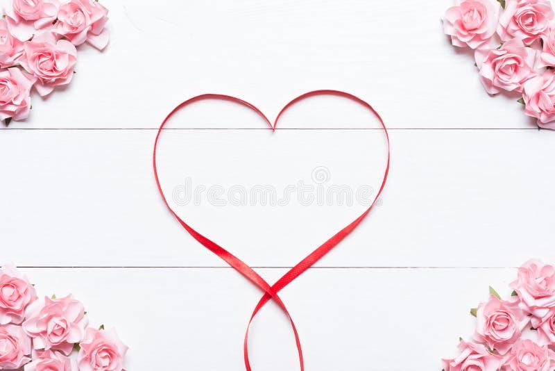 Het rode symbool van het linthart met roze rozen op witte houten lijst royalty-vrije stock foto