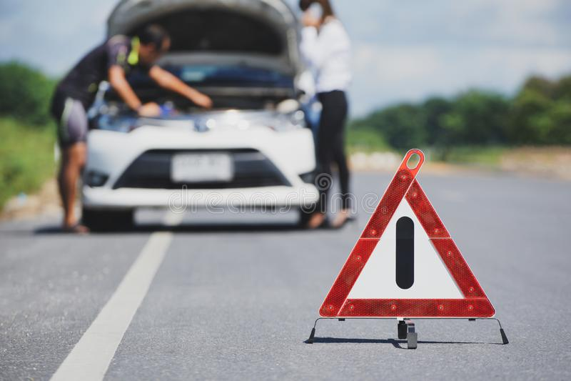 Het rode teken van het noodsituatieeinde en witte auto na ongeval op de weg stock foto