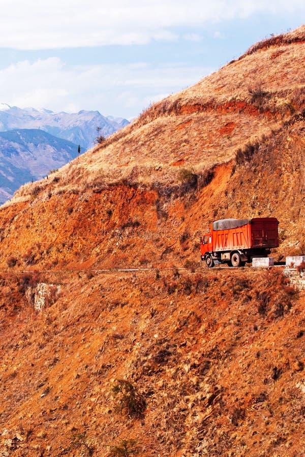 Het rode vrachtwagen drijven op een bergweg op de winterschemer, fantastisch landschap van rode bergrand en de achtergrond van sn royalty-vrije stock foto