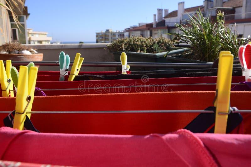 Het rode Wasserij Drogen, Kleurrijke Spelden, Huisinstallaties, Balkon stock afbeelding