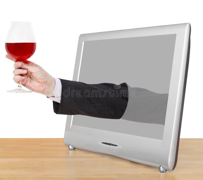 Het rode wijnglas in mannelijke hand leunt TV-uit het scherm stock foto's