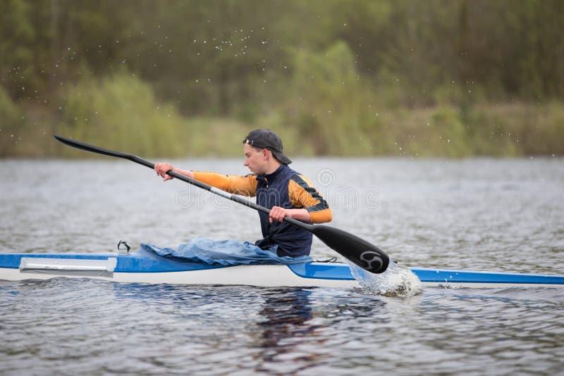 Het roeien basis Opleiding in het roeien Tiener in een sportenboot met roeispanen stock afbeelding
