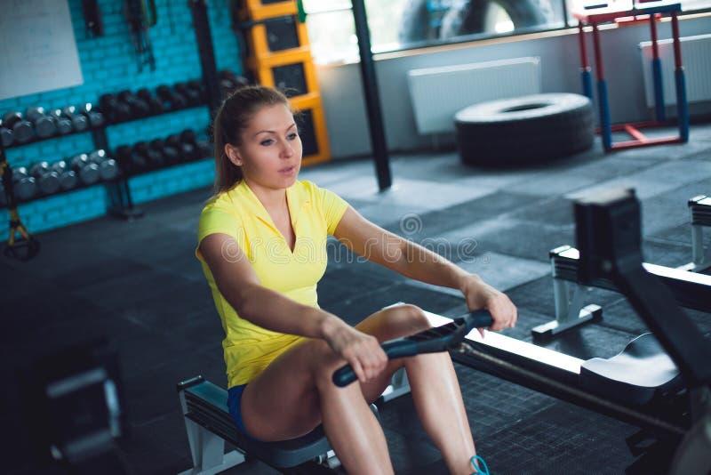 Het roeien in de gymnastiek Jonge vrouw die gebruikend het roeien machine opleiden royalty-vrije stock afbeelding