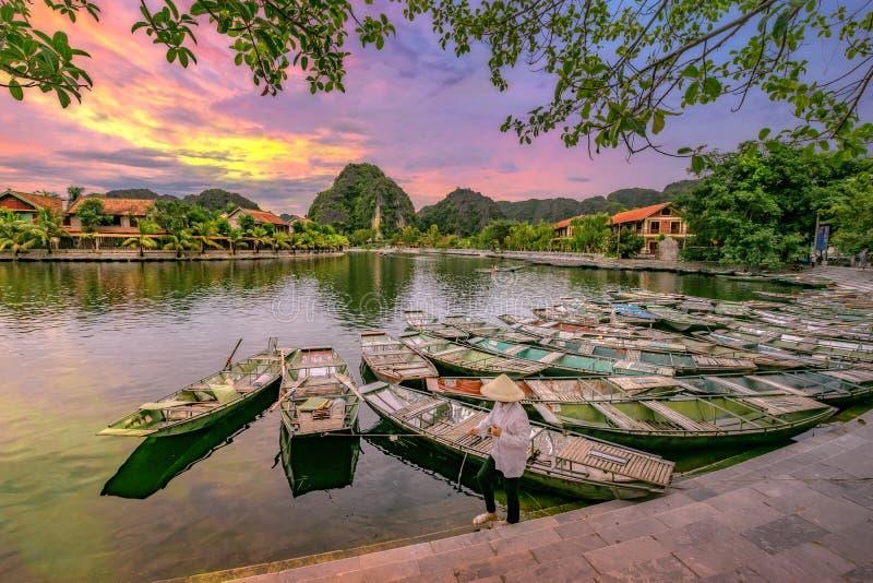 Het roeien van boot die op passagiers bij zonsopgang, Hoa Lu Tam Coc, Hoi wachten stock fotografie