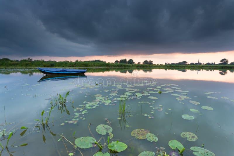 Het roeien van boot op een klein meer tijdens een bewolkte zonsondergang stock foto