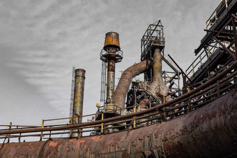Het roesten staalfabriek industriële complex tegen een koude grijze hemel stock afbeeldingen