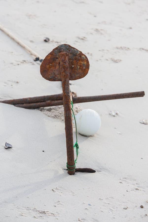Het roestige vaste lichaam van het botenanker in het zand royalty-vrije stock foto
