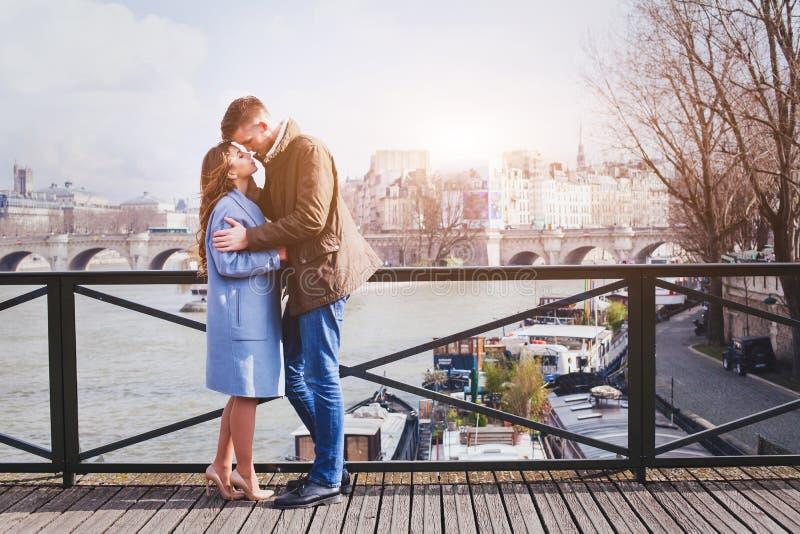 Het romantische dateren, het jonge paar kussen op de brug in Parijs stock afbeeldingen
