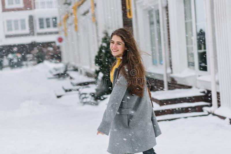 Het romantische Europese meisje in lange grijze laag kruist de straat en het bekijken sneeuwval Openluchtportret van dromerig blo royalty-vrije stock foto's
