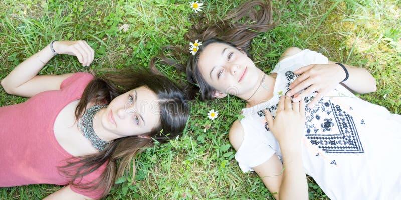 Het romantische Gelukkige meisje die van tienersvrienden op bloemweide liggen royalty-vrije stock fotografie