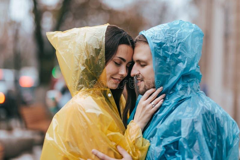 Het romantische houdende van paar, de kerel en zijn meisje in de regenjassen bevinden zich face to face op de straat in de regen stock afbeeldingen