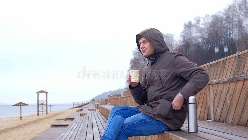 Het romantische jonge mens ontspannen op het strand met, het drinken de hete thee of de koffie van thermosflessen Kalme en comfor stock afbeeldingen