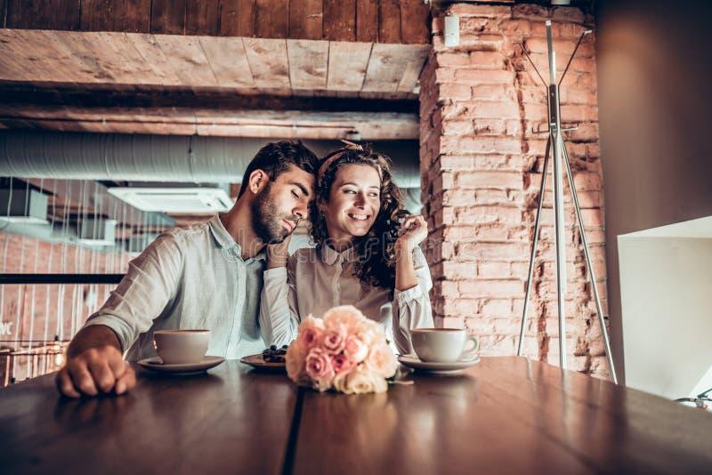Het romantische jonge paar brengt tijd in restaurant door stock foto's