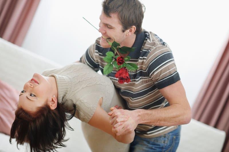 Het romantische jonge paar dat danst met nam toe royalty-vrije stock afbeeldingen