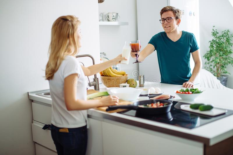 Het romantische jonge paar koken samen in de keuken, die een grote tijd hebben samen stock foto