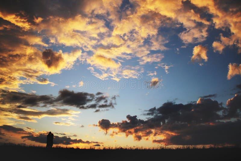 Het romantische jonge paar kussen op zonsondergang stock afbeelding