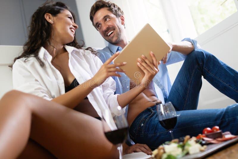 Het romantische jonge paar ontspannen samen in slaapkamer, het drinken wijn en het gebruiken van tablet royalty-vrije stock afbeeldingen