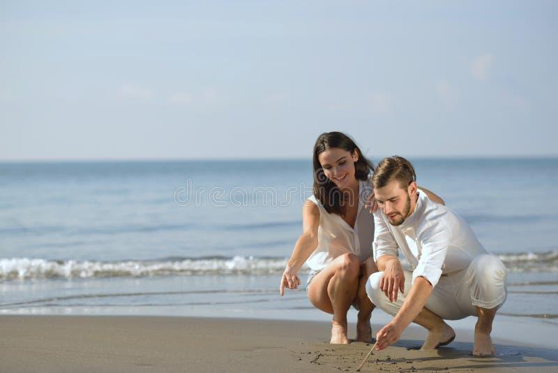 Het romantische jonge paar trekt hartvormen in het zand terwijl op wittebroodsweken De liefdeconcept van het de zomerstrand royalty-vrije stock foto's