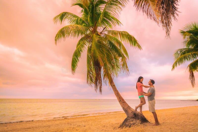 Het romantische jonge paar van de zonsondergangwandeling in liefde die op palmen bij roze schemer omhelzen betrekt hemel Romaans  stock afbeelding
