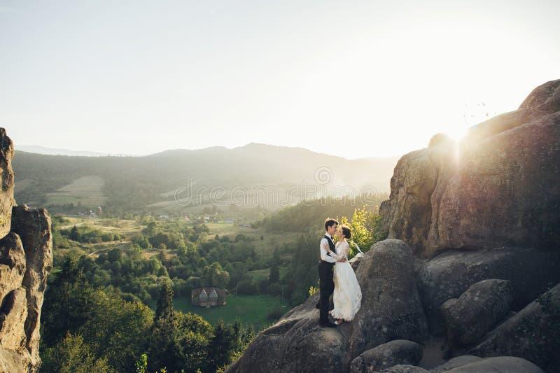 Het romantische jonggehuwdepaar stellen in zonsonderganglichten op majestueuze roc stock afbeelding