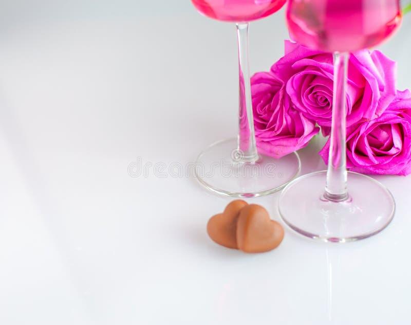 Het romantische landschap met chocoladeharten, nam bloemen en gla twee toe stock afbeelding