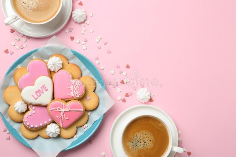 Het romantische ontbijt met hart vormde koekjes en koppen van koffie op kleurenachtergrond royalty-vrije stock afbeeldingen