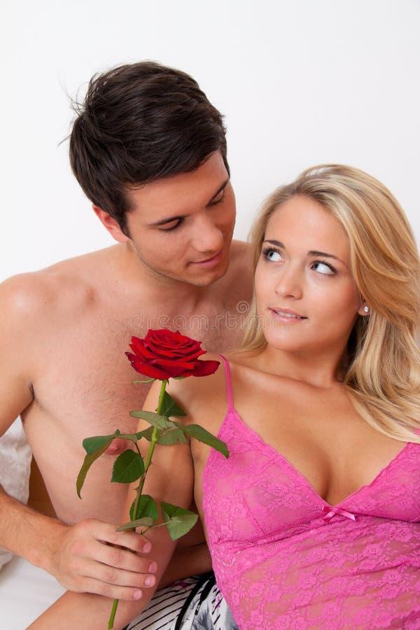 Het romantische paar in bed met nam toe. Huw de man. royalty-vrije stock foto