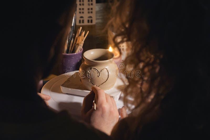 Het romantische paar die in liefde in de workshop van de ambachtstudio samenwerken en trekt een hart op een kleipot stock foto