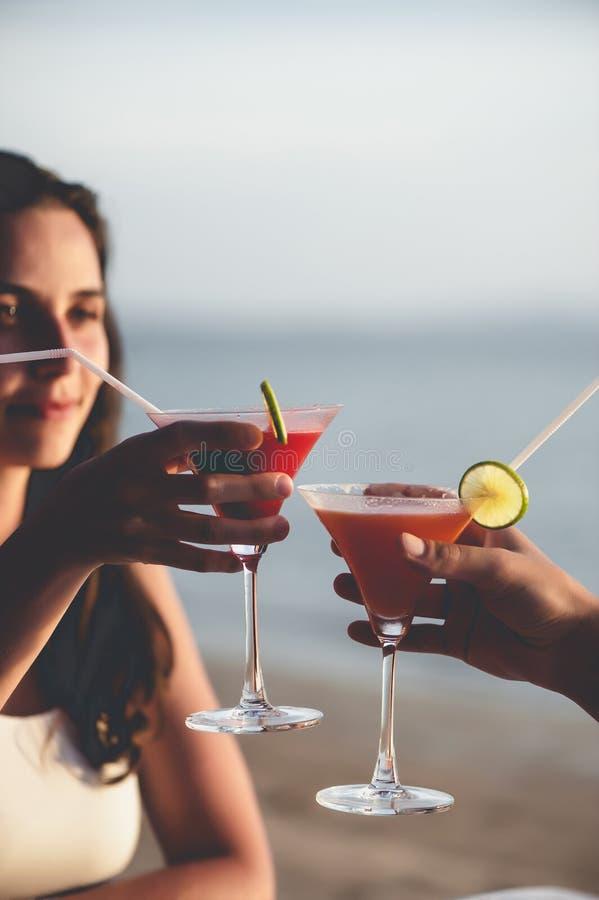 Het romantische paar geniet van zonsondergang in restaurant op de strand het drinken cocktails stock afbeeldingen