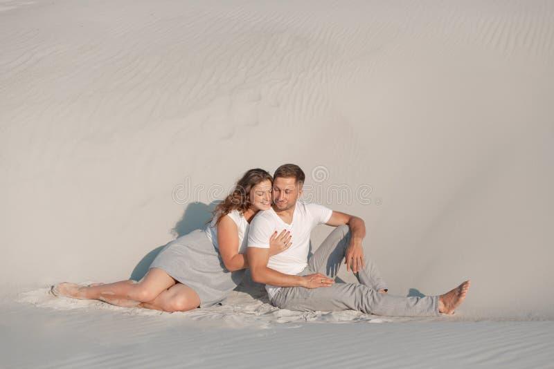 Het romantische paar zit op wit zand en huggins, in woestijn royalty-vrije stock foto's