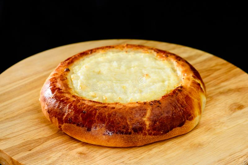 Het ronde heerlijke broodje van het zure roomdessert op houten raad, donkere bac royalty-vrije stock fotografie