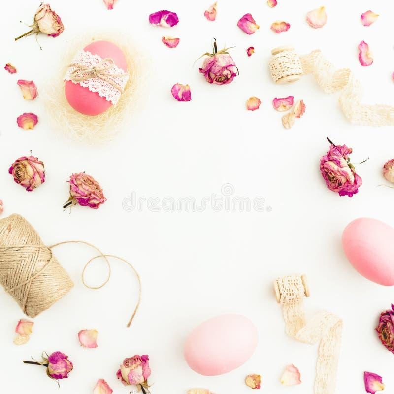 Het ronde kader van de roze eieren van Pasen met streng, rozenbloemen en banden op witte achtergrond, Hoogste mening, Vet lag De  royalty-vrije stock foto's