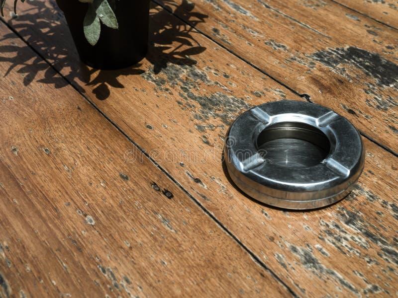 Het ronde lege asbakje van het staalmetaal op houten lijst royalty-vrije stock foto