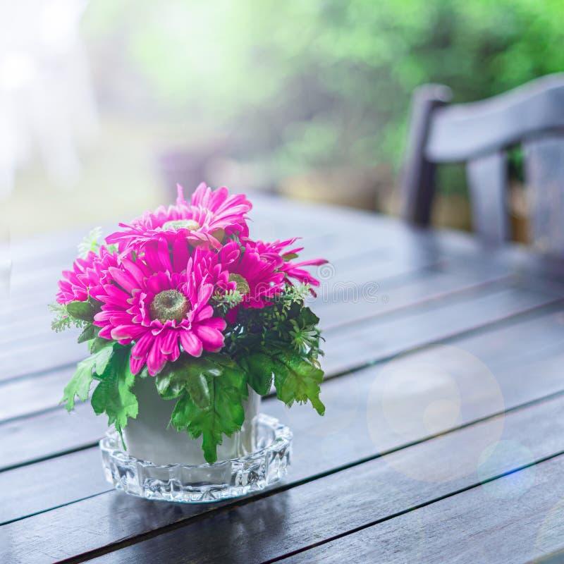 Het rood, de bloemen van Bourgondië in een pot bevindt zich op een houten lijst, de groene vage achtergrond van de straatkoffie,  stock foto's