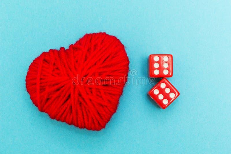 Het rood dobbelt en hart op de blauwe achtergrond stock fotografie