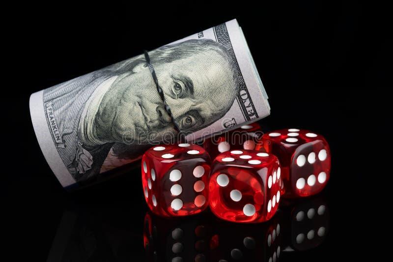 Het rood dobbelt voor het gokken voor geld op een zwarte achtergrond stock afbeelding