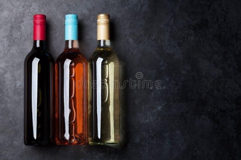 Het rood, nam en witte wijnflessen toe royalty-vrije stock afbeeldingen
