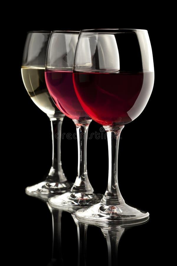 Het rood, nam en witte wijnglazen in een zwarte backgr toe stock foto