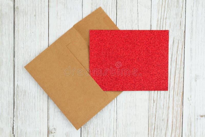 Het rood schittert lege groetkaart en de envelop op doorstaan vergoelijkt geweven houten achtergrond royalty-vrije stock foto's