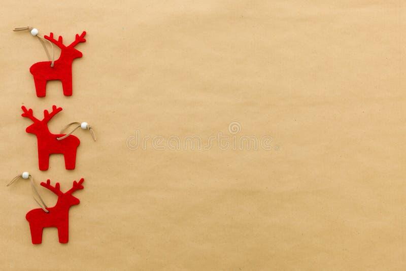 Het rood voelde rendier op een natuurlijke pakpapierachtergrond met ruimte voor exemplaar stock afbeelding