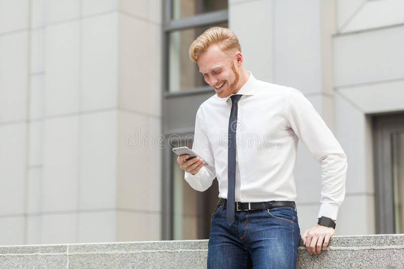 Het roodharige en de gebaarde bedrijfsmens hebben een videoconferentie in hes slimme telefoon Bedrijfs concept stock afbeeldingen