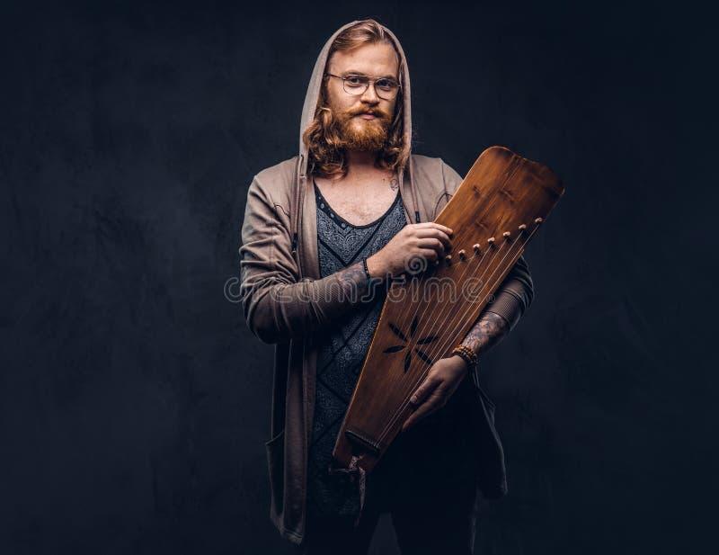 Het roodharige hipster mannetje met lang luxuriant haar en volledige baard gekleed in een hoodie en een t-shirt houdt een Rus tra stock fotografie