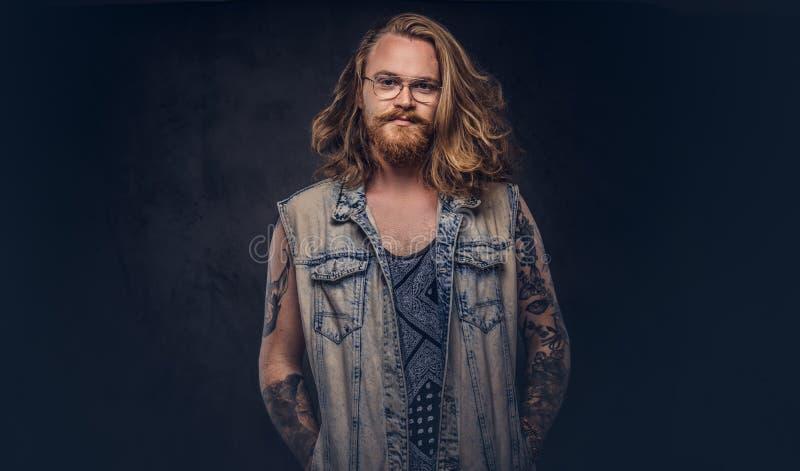 Het roodharige hipster mannetje met lang luxuriant haar en volledige baard gekleed in vrijetijdskleding die stellen met dient zak royalty-vrije stock afbeeldingen